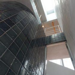 玄関フロアの吹き抜け。天上まで一気に抜いた高さ10メートルの吹き抜けです。天上部には明りとり用のトップライトを設置しました。リビングに続くドアを開くと天空に浮く2階廊下のブリッジが現れます。